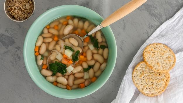 Ciotola piatta con zuppa di fagioli bianchi e cracker