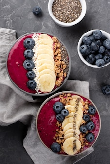 Flat lay of bowls with breakfast desserts and assortment of fruits and cereal