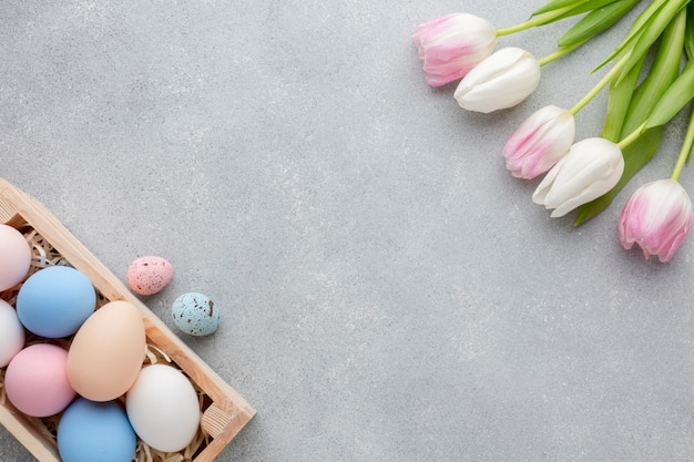 Flat lay of box with colorful easter eggs and tulips