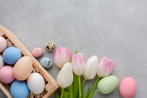 Flat lay of box with easter eggs and colorful tulips
