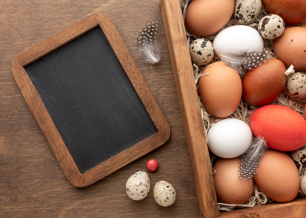 Flat lay of box with eggs for easter and blackboard