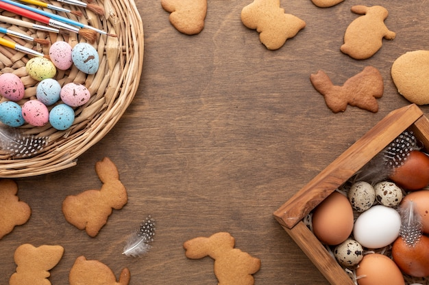 Flat lay of box with eggs for easter and bunny shaped cookies