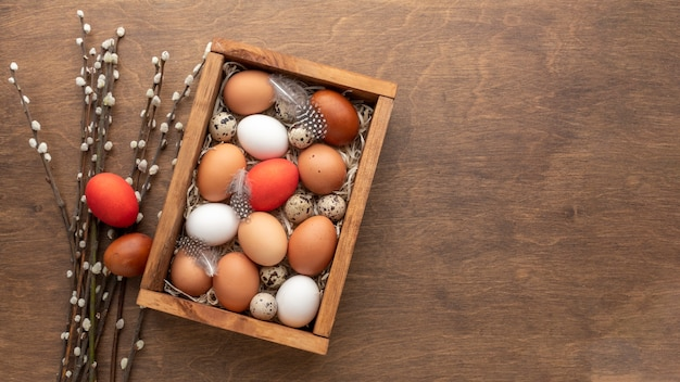 Flat lay of box with eggs for easter and copy space