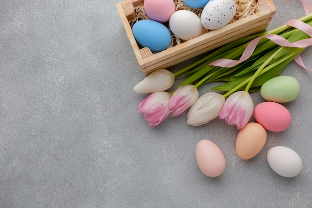 Flat lay of box with multicolored easter eggs and tulips
