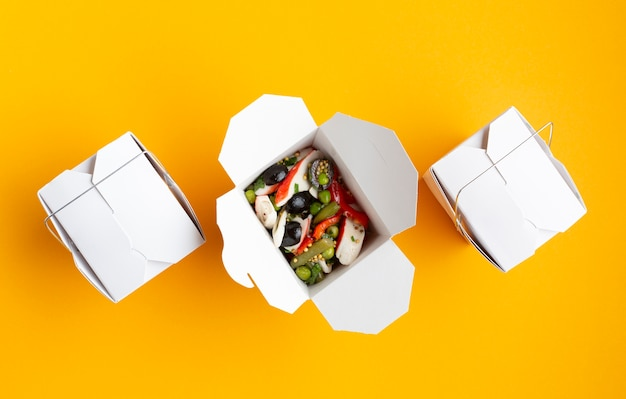 Flat lay boxes with salad on yellow background