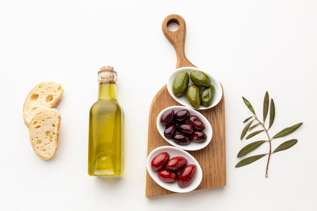 Flat lay bread slices and purple red green olives with olive oil bottle