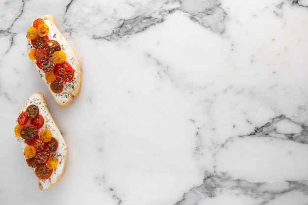 Flat lay bread with cream cheese and cherry tomatoes on marble with copy-space