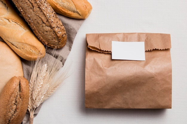 Flat lay breads mix with paper packaging and wheat