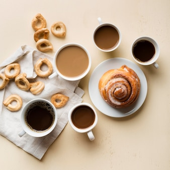 Flat lay breakfast arrangement with coffee and pastries