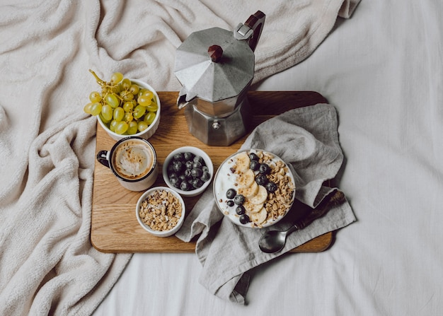 Flat lay of breakfast in bed with cereal and coffee