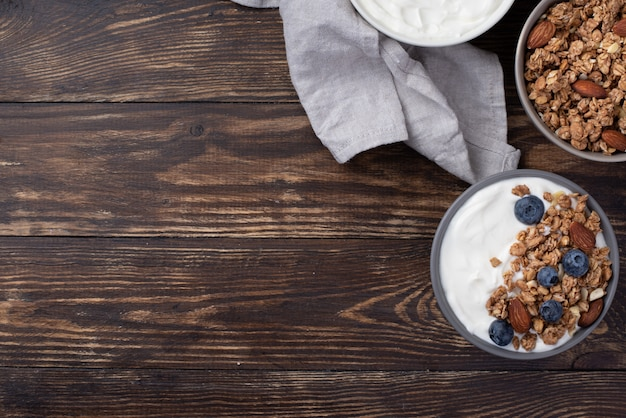 Flat lay of breakfast cereal with blueberries and yogurt