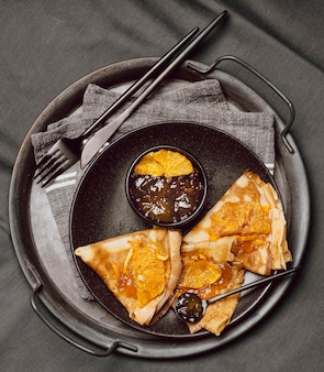 Flat lay of breakfast crepes with jam on bed