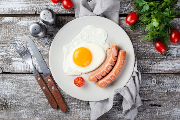 Flat lay of breakfast sausages and egg on plate with tomatoes and cutlery