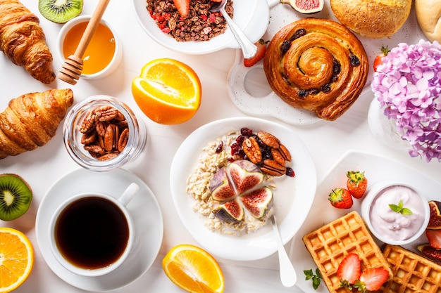 Flat lay of breakfast table with oatmeal, waffles, croissants and fruits,