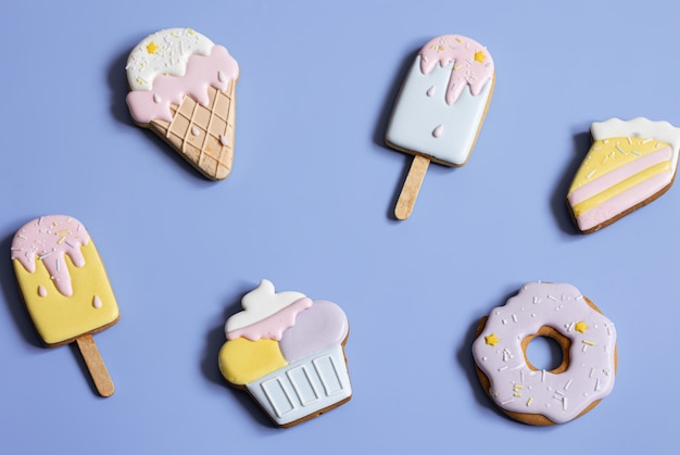 Flat lay of bright glazed gingerbread cookies on a blue background copy space.