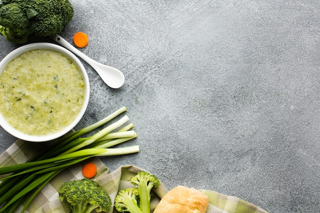 Flat lay broccoli bisque in bowl vegetables and spoon with copy space