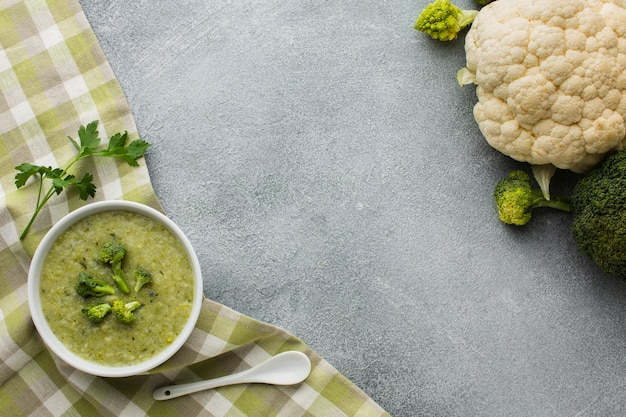 Flat lay broccoli bisque on kitchen towel and cauliflower with copy space
