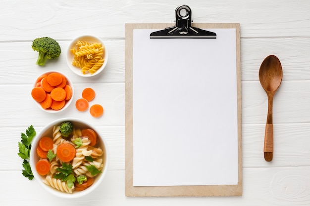 Flat lay broccoli carrots and fusilli in bowl with blank notebook