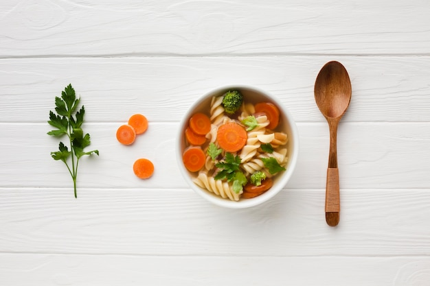 Flat lay broccoli carrots and fusilli in bowl with wooden spoon