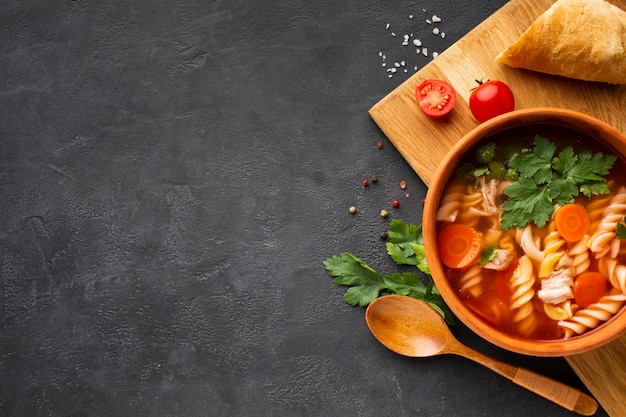 Flat lay broccoli carrots and fusilli soup in bowl with bread tomatoes and wooden spoon with copy space