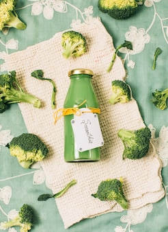 Flat lay broccoli smoothie in a bottle