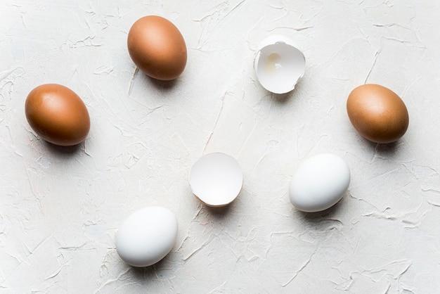 Flat lay broken eggs on white background