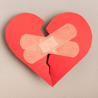 Flat lay broken heart with band-aids