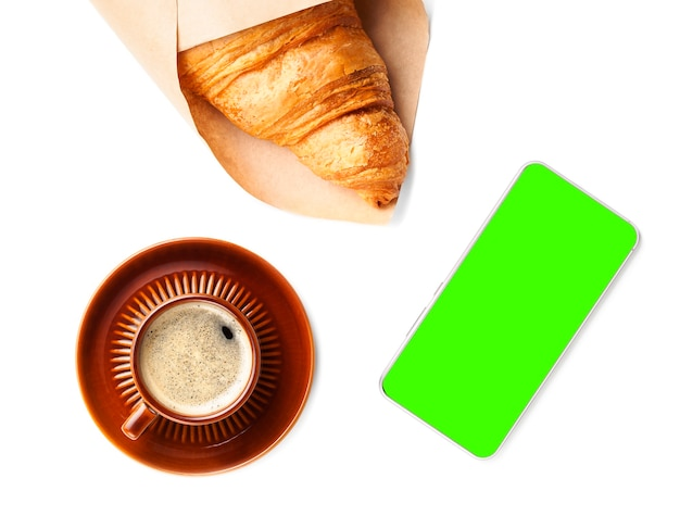 Flat lay of brown cup of black coffee with croissant and phone green screen