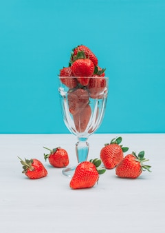 Flat lay bunch of strawberries in glass with several around this on blue background. horizontal