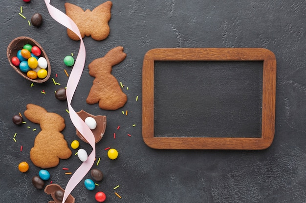 Flat lay of bunny shaped cookies and chocolate eater eggs with blackboard