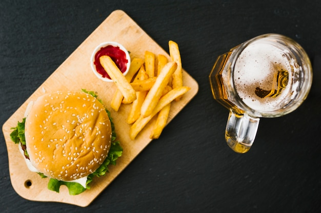 Flat-lay burger and fries on wooden board with beer
