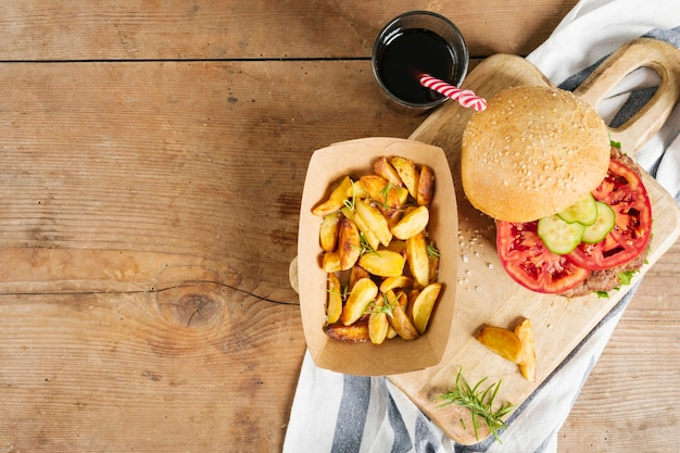 Flat-lay burger and fries on wooden board