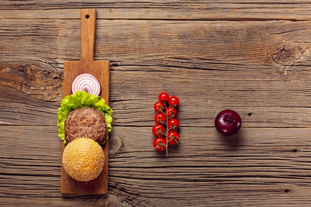 Flat lay burger ingredients on a wooden table