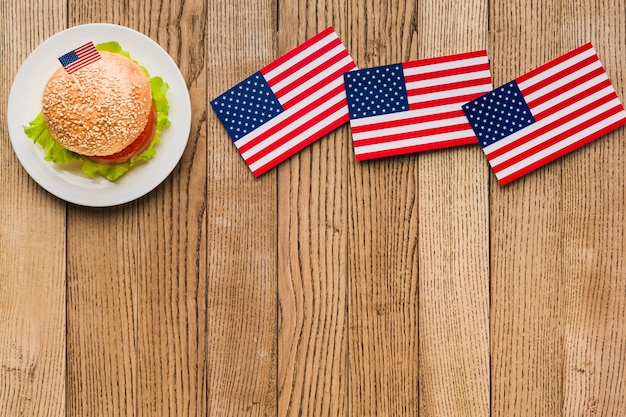Flat lay of burger on plate with american flags on wooden surface and copy space