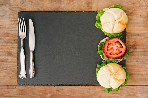 Flat-lay burger on slate with cutlery