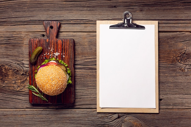 Flat lay burger with mock-up clipboard