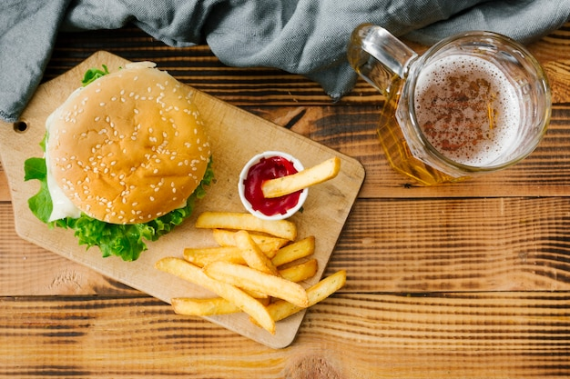Flat-lay burger on wooden board with beer