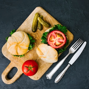 Flat-lay burger on wooden board with cutlery