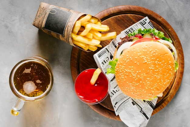Flat-lay burger on wooden board with fries and beer