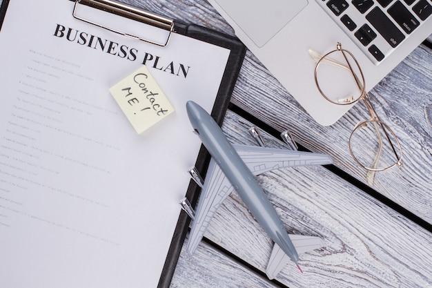 평평한 평신도 사업과 여행 컨셉입니다. 사업 계획과 나무 탁자에 있는 장난감 비행기. 저에게 연락하십시오.