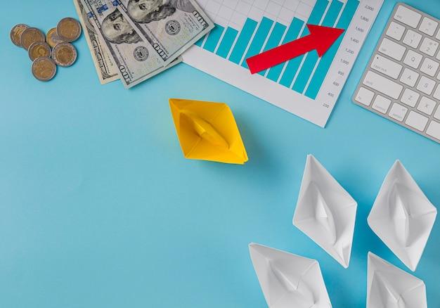 Disposizione piatta di articoli aziendali con grafico di crescita e barchette di carta
