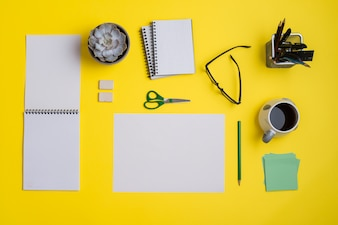 Flat lay business workplace with office supplies and coffee on yellow backdrop