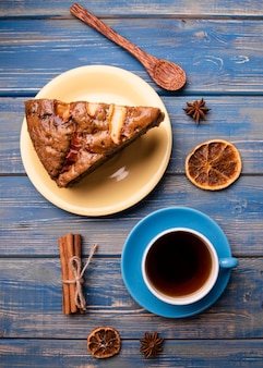 Flat lay of cake slice with cup of tea