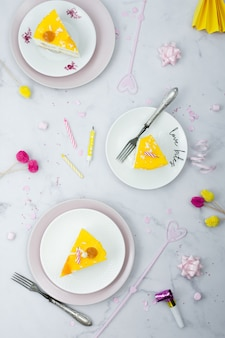Flat lay of cake slices on plates with birthday decorations
