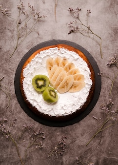 Flat lay of cake with banana slices and kiwi