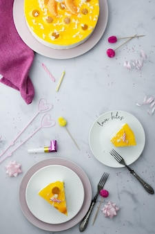 Flat lay of cake with slices and birthday decorations