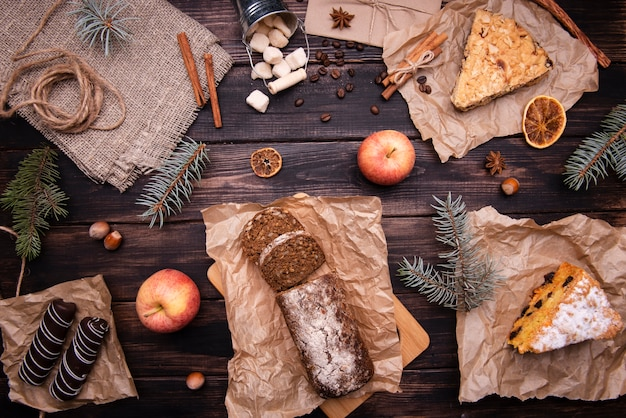 Flat lay of cakes and chocolate desserts with pine and apples