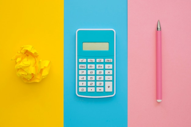 Flat lay of calculator with pen and crumpled paper