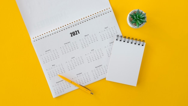 Flat lay calendar and copy space notepad