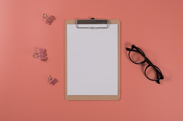 Flat lay calendar with clipboard and glasses on living coral color background. blank space. top view.